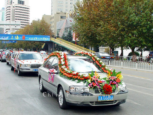 Cars bedecked with flowers take Bride and Groom and their guests to a Wedding Reception in Yunnan.