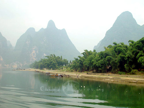 The Li River looks like a liquid jade ribbon as it reflects the green of the luxurious vegetation that lines its banks.