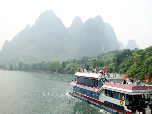 Visitors crowd the observation decks to admire the picturesque landscape that unfolds before them as they proceed along the Li River.
