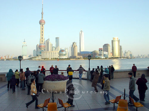 Pedestrians in the city Bund and the opposite Oriental Pearl TV Tower in the Pudong New Area, Shanghai