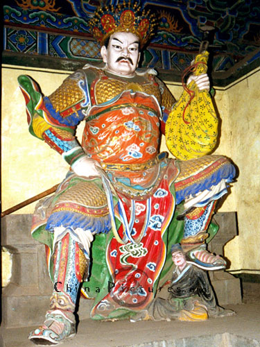 Looking like a character in the Peking Opera, this Heavenly King poses with a lute in his life hand while crushing a devil under his foot.